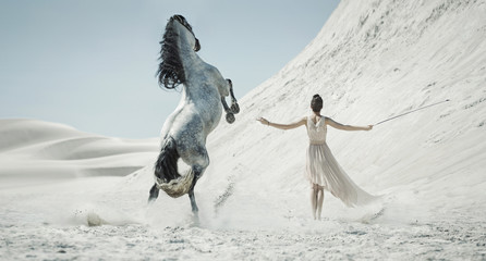 Pretty lady with huge horse on the desert