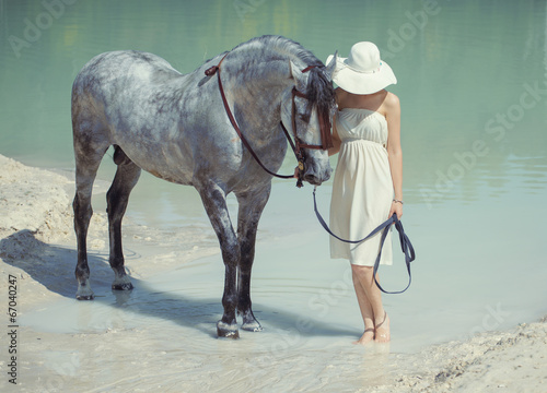 Young smart lady walking with the horse - 67040247