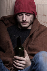 Drunk homeless man with a bottle of wine
