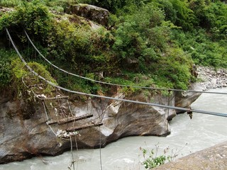 Broken foot bridge over a Himalayan river, Annapurna, Nepal