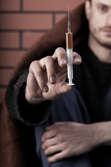 Homeless drug addict man with syringe in hand