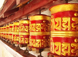 Painted Tibetan Buddhist prayer wheels at a temple in Nepal