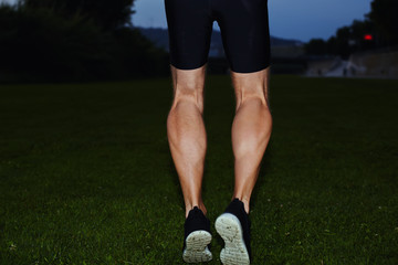 Athletic male runner jogging in the park, muscular legs