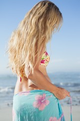 Pretty blonde in bikini and sarong on the beach