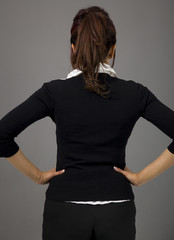 Rear view of Indian businesswoman standing with her arms akimbo
