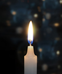 Burning candles on black blue background