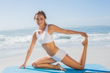 Gorgeous fit blonde in seated yoga pose on the beach