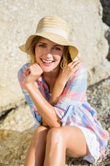 Pretty blonde smiling at camera at the beach