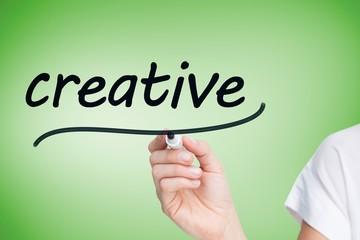 Businesswoman writing the word creative