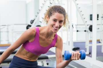 Pretty fit woman lifting blue dumbbell sitting on bench