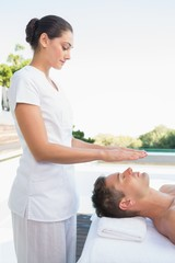 Peaceful man getting reiki treatment poolside
