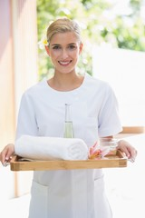 Smiling beauty therapist holding tray of beauty treatments