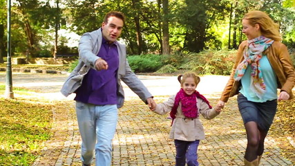 Happy young parents with daughter in park