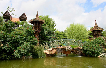 Decorative bridge over green lake surrounded by shrubs