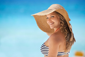 Portrait of woman with straw hat at beach smiling