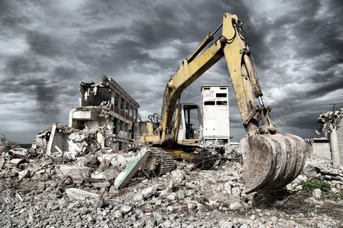 Bulldozer removes the debris from demolition of old buildings - 67048461