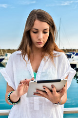 Young girl relaxing with tablet at the dock