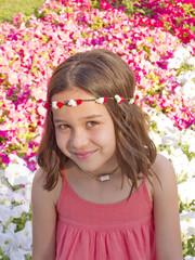 Niña con diadema de flores entre flores rojas y blancas