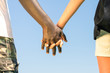 Multiracial couple walking hand in hand against a blue sky