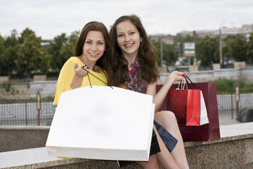Smiling girls opened a package with purchase