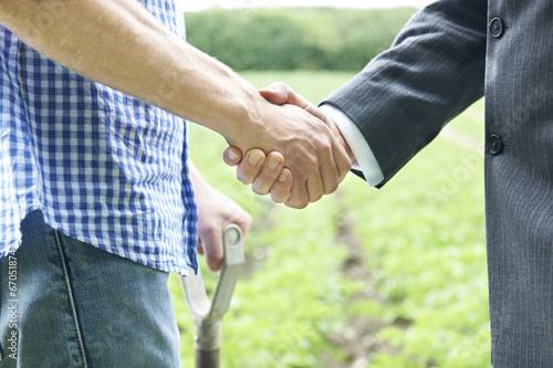 Leinwanddruck Bild Farmer And Businessman Shaking Hands