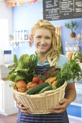 Woman Working In Shop With Basket Of Fresh Produce