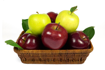 Fresh red and green apples with leaves in wicker basket isolated