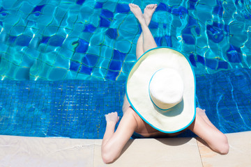 young woman in big hat relaxing in the swimming pool