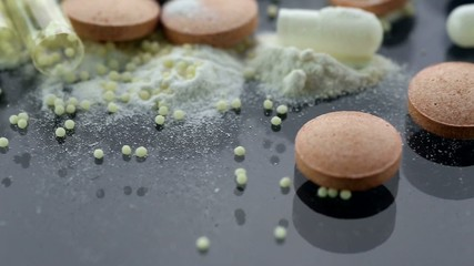 Drug Addiction Concept. Macro film of powder by open pills.