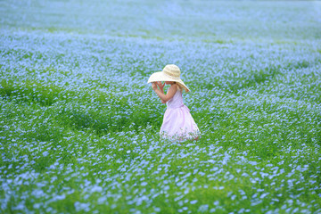 Young child in a flower field, wearing a large sun hat