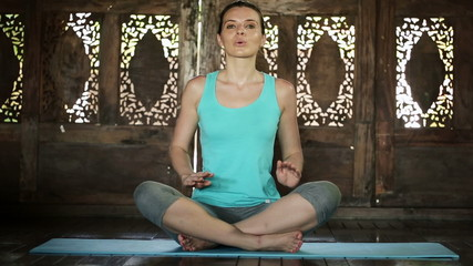 Attractive woman doing breathing exercise at home