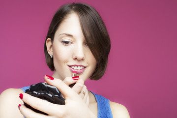 Beautiful young woman on pink background doing makeup.