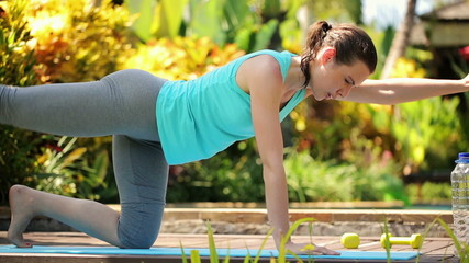 Young attractive woman exercising in the garden