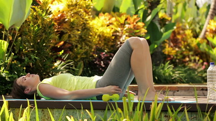 Woman resting, drink water after sit-ups exercise in garden