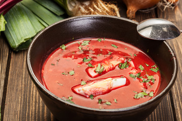 Beetroot soup with egg and vegetables in a bowl