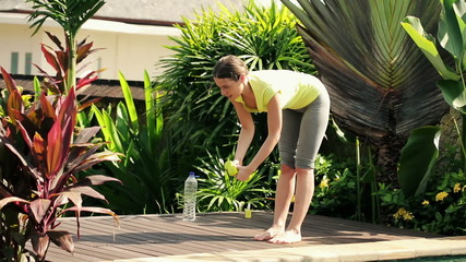 Young woman exercising with dumbbells in the garden