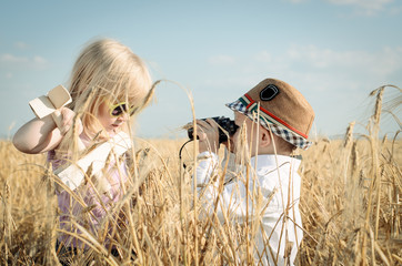 Two little children playing in a wheat field