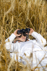 Cute boy lying down in a field of ripe wheat