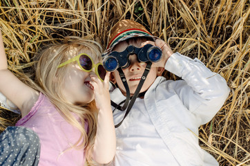 Boy and girl playing in grass with binoculars