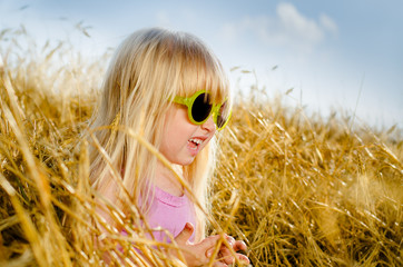 Cute little girl wearing sunglasses, in a warm day