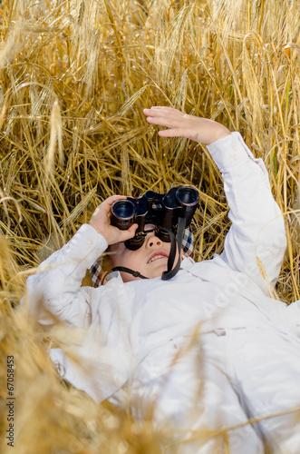 Cute boy lying down in a field of ripe wheat