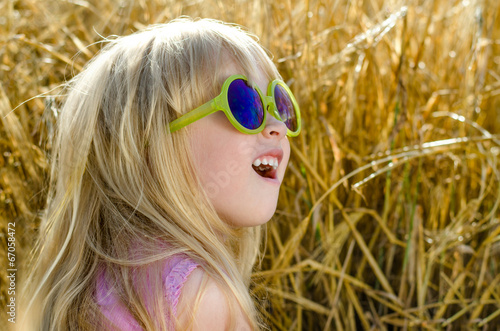 Cute little girl in sunglasses with a look of awe