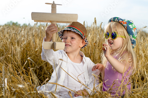 Two young children playing with a model plane