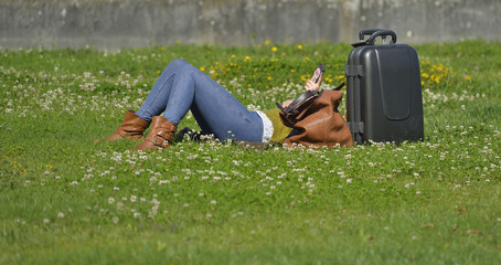 woman resting with her suitcase and using your smartphone