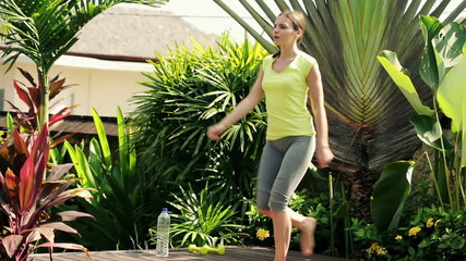 Young beautiful sporty woman exercising on platform in garden