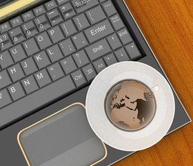 Coffee cup and saucer with a globe on computer keyboard