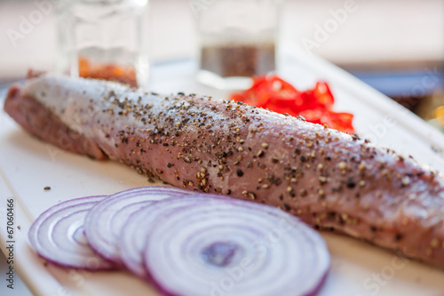 Raw pork fillet with freshly ground pepper and red onion
