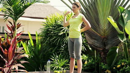 Young woman exercising, stretching in beautiful garden