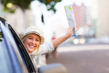 female tourist traveling in a car waving a map