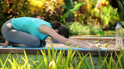 Woman stretching, doing japanese sit in the garden
